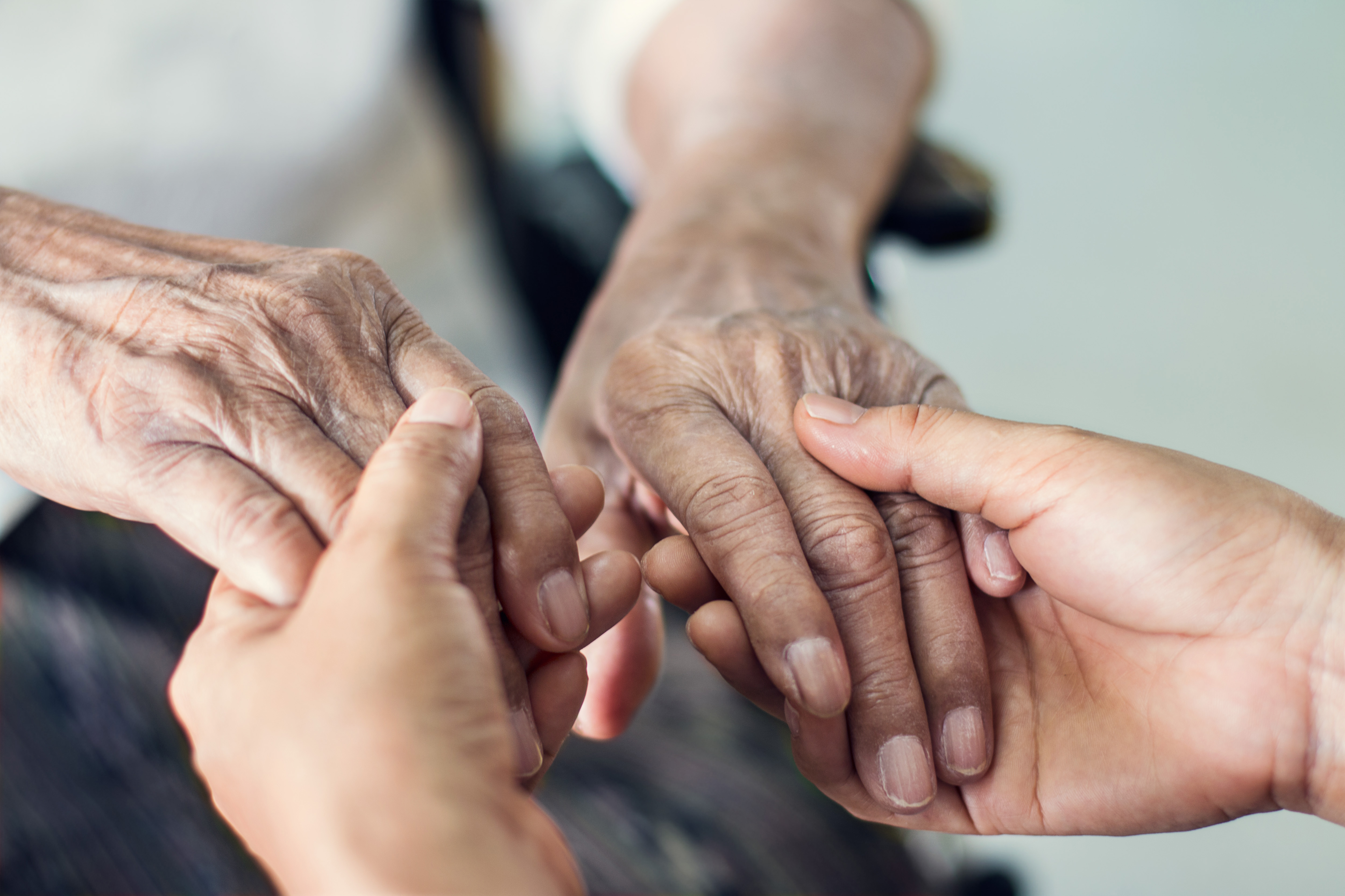 Close up hands of helping hands elderly home care. Mother and daughter. Mental health and elderly care concept